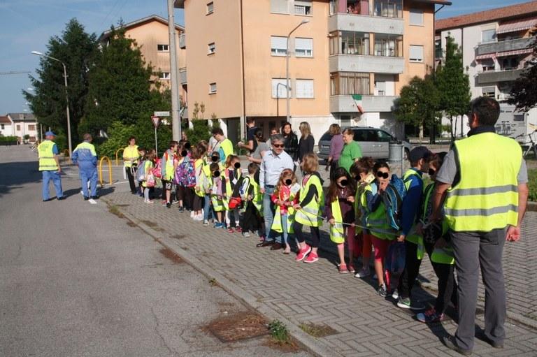 Foto  Alunni in fila accompagnati da volontari